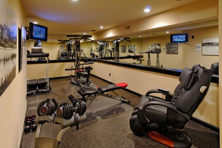 Image of a luxury indoor exercise area showing several types of home gym equipment