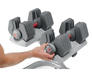 Preview image of a set of Universal Power-Pak 445 adjustable dumbbells sitting on a storage rack