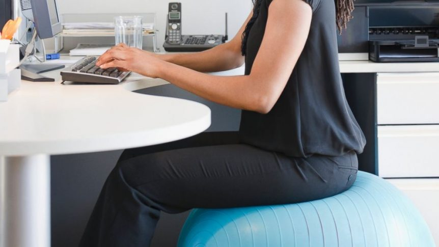 Image of a woman sitting on an exercise ball at work