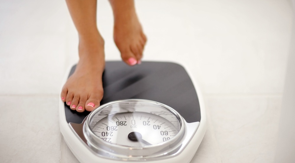 Image of a woman checking her weight on a bathroom scale