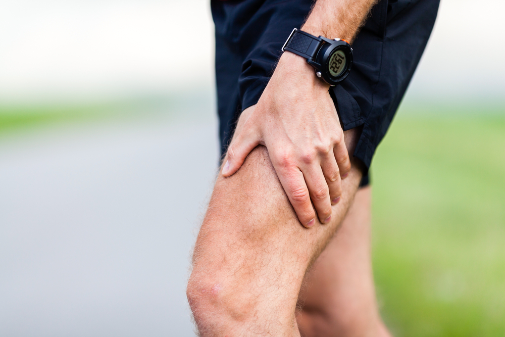 Image of a man grabbing his leg muscle wondering how to get rid of muscle soreness
