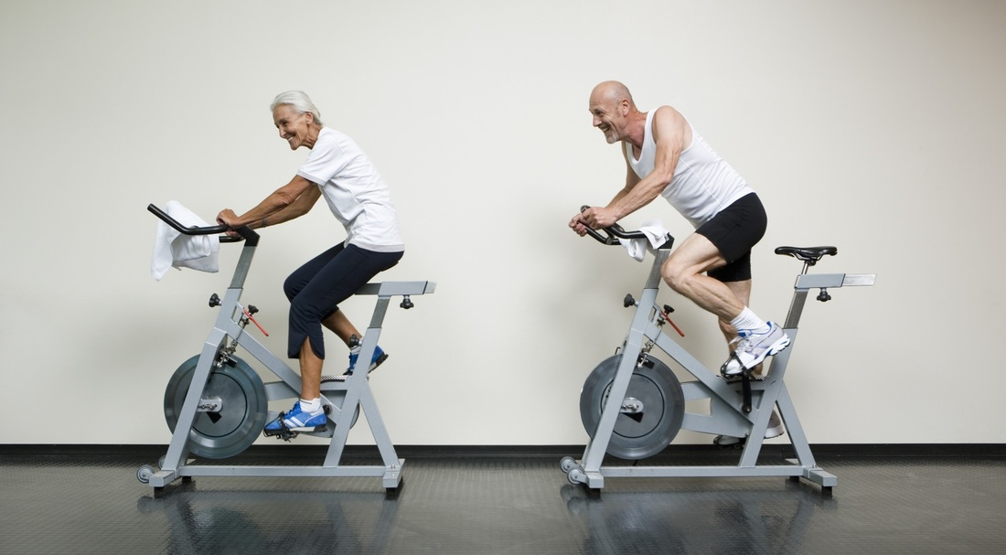 Image of two seniors riding exercise bikes