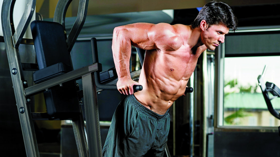 Image of a man doing chest dips on a dip station