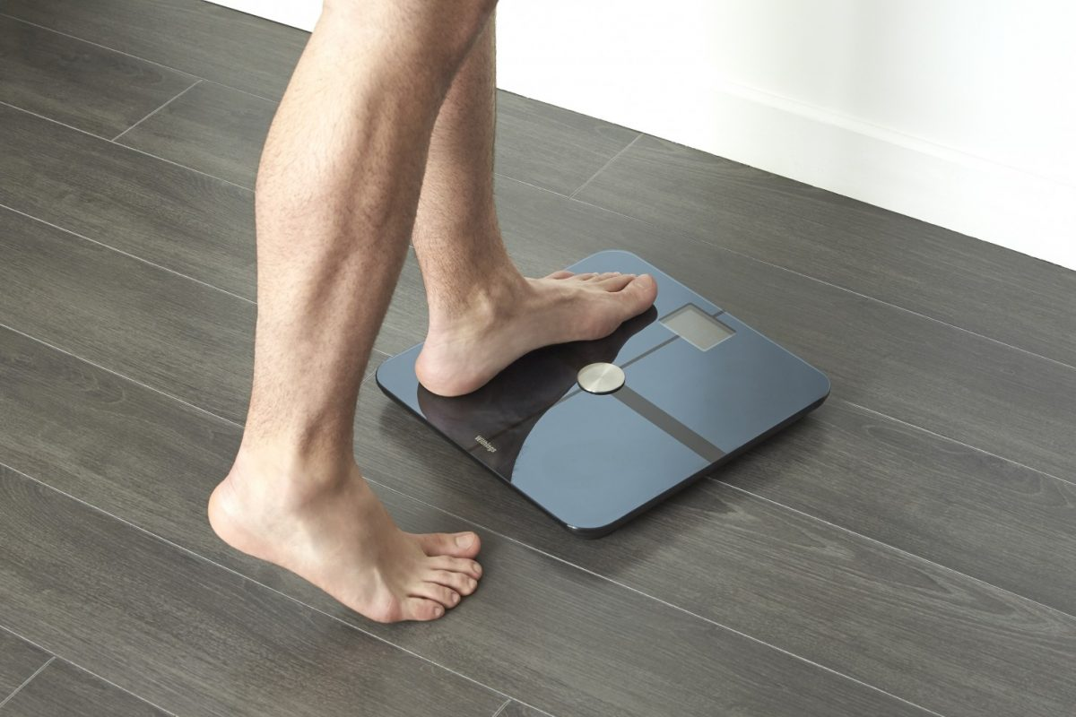 Image of a man stepping on a digital scale to measure weight