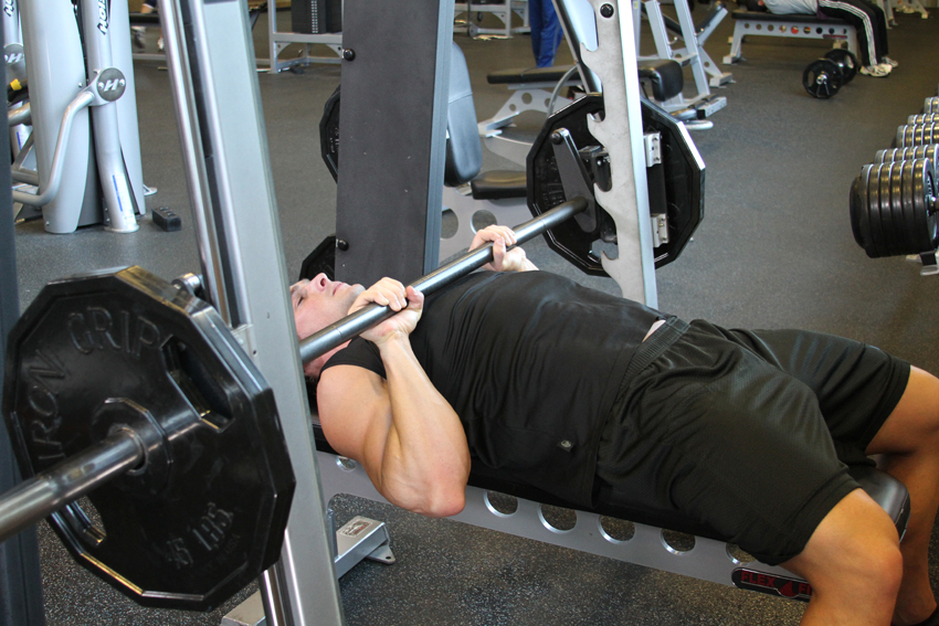 Image of a man doing a close-grip bench press on a smith machine