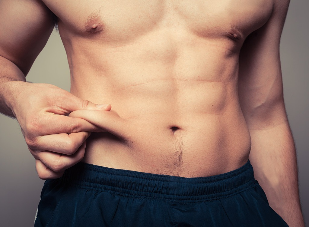 Image of a fit man pinching his belly fat
