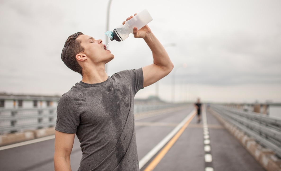 Image of a man drinking water after a workout