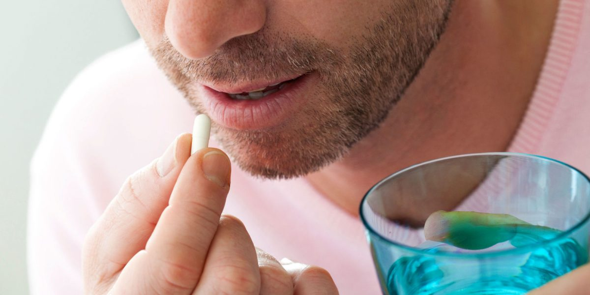Image of a man taking a fat burner pill