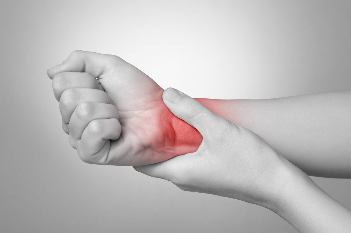 Image of a woman holding her wrist in pain