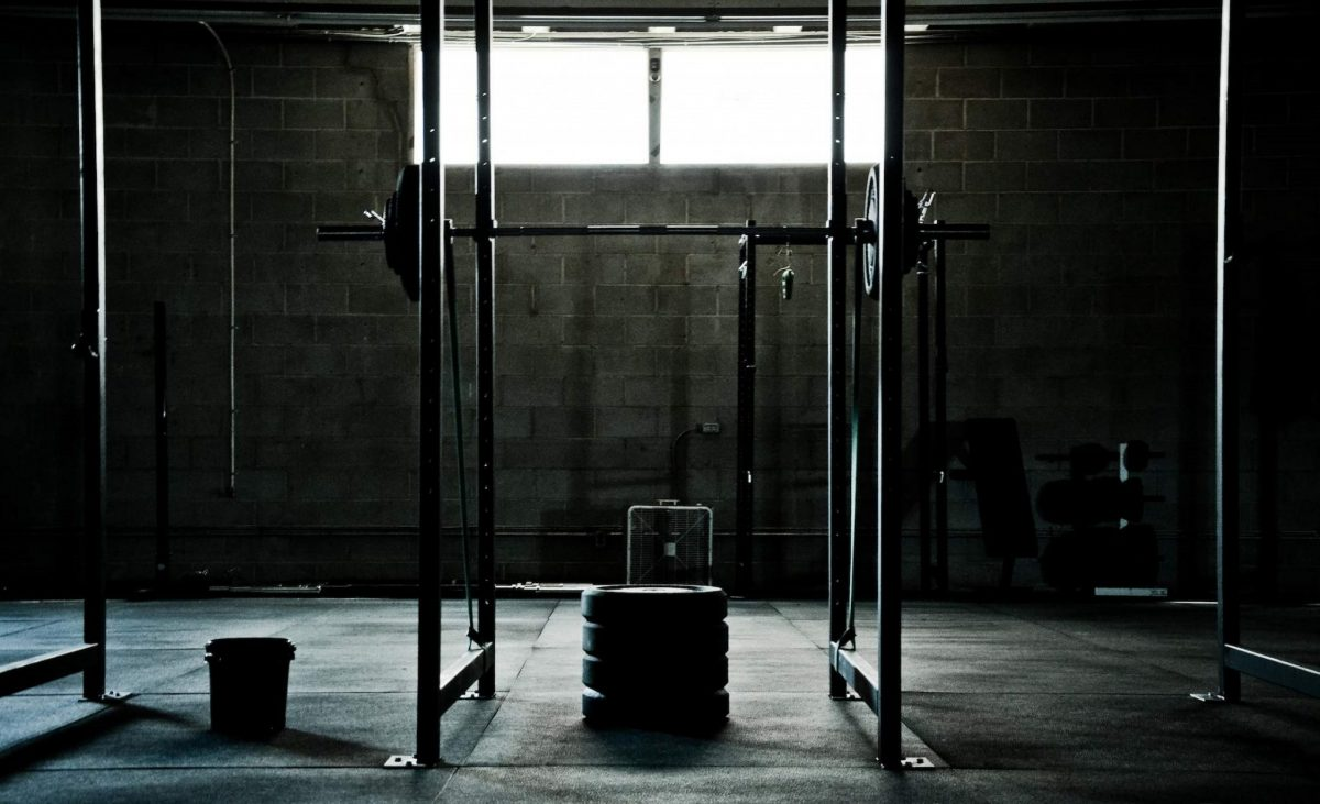 Image of a squat rack in a dark home gym