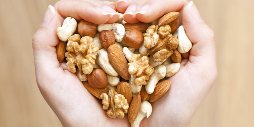 Image of a woman holding a handful of nuts in a heart shape