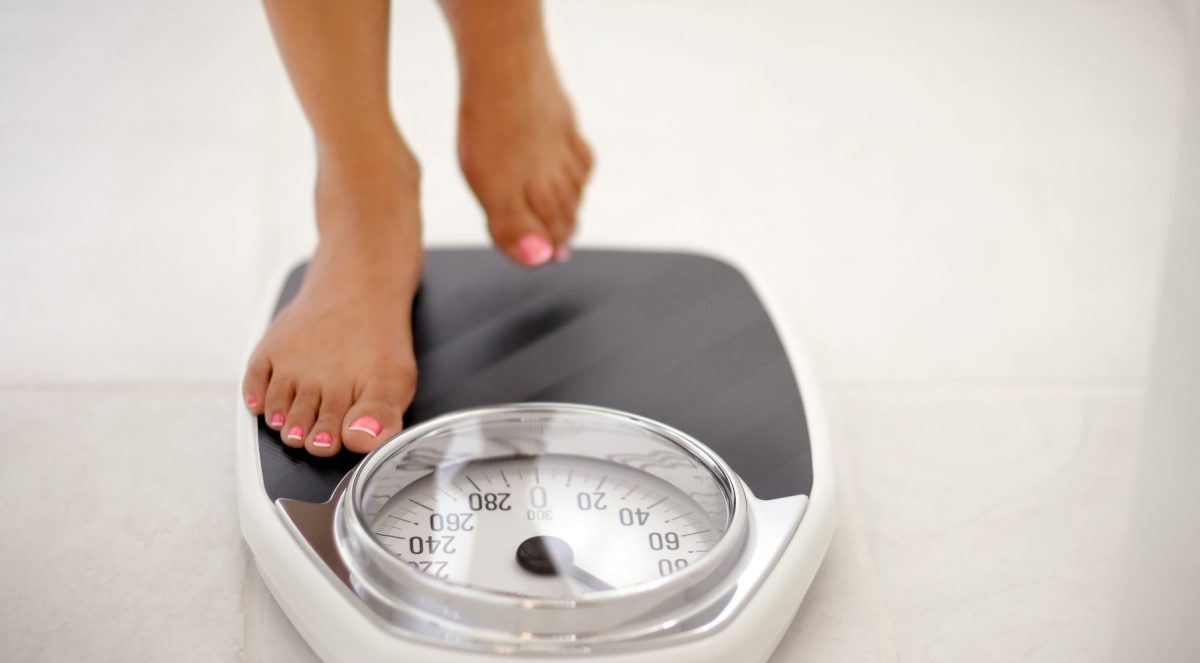 Image of a woman stepping on a bathroom scale
