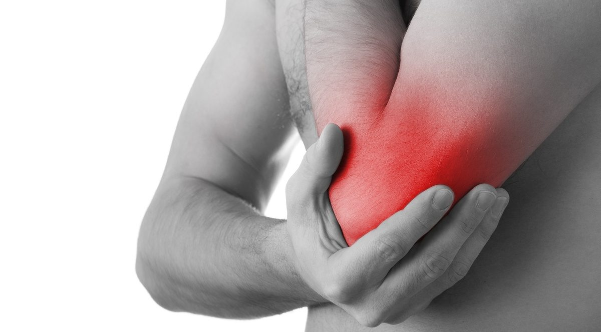 Image of a man holding his arm in pain from tennis elbow symptoms