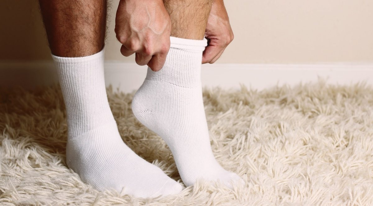 Image of a man putting on socks