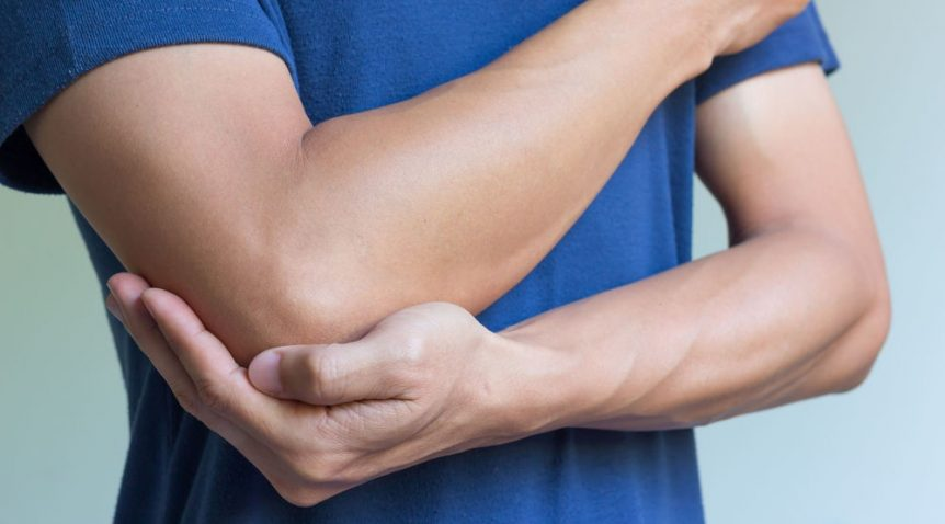 Image of a man holding his arm in pain from tendonitis