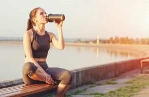 Woman sitting by the lake drinking from an ice shaker bottle